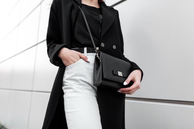 Молодая женщина в модном черном пальто в винтажных белых джинсах с сумочкой