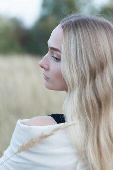 Молодая женщина в поле спиной к камере с букетом пшеницы.