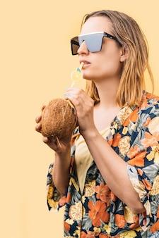 Молодая женщина в цветочной рубашке и больших солнцезащитных очках пьет кокосовый коктейль с трубочкой