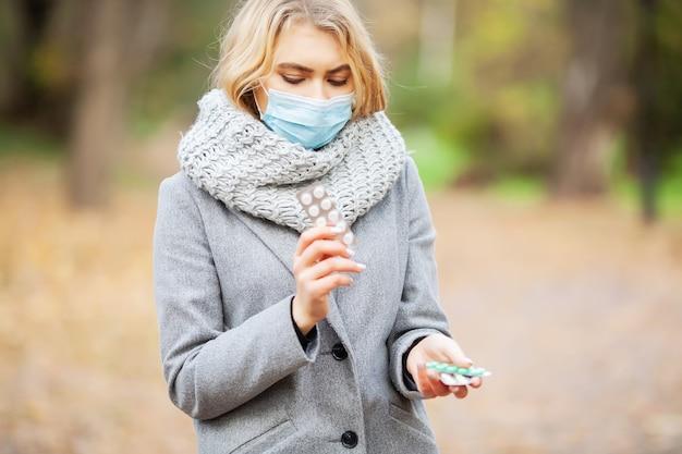 Молодая женщина в сером пальто гуляя в парк осени с маской