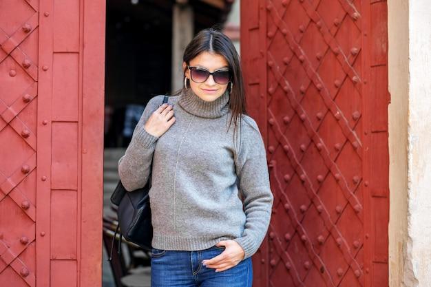 Молодая женщина в сером вязаном свитере выходя