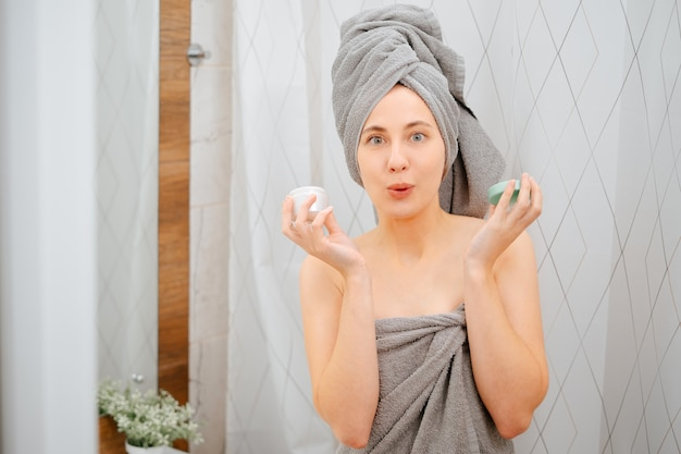 욕실 배경에 회색 수건을 두른 젊은 여성은 주름을 위한 혈청 한 병을 들고 있다