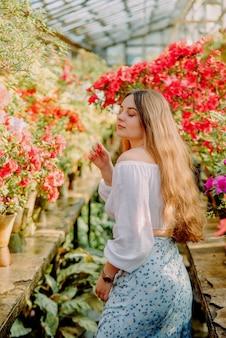 ツツジと温室の若い女性