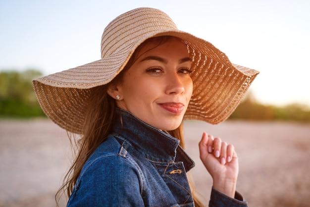 青い海に帽子をかぶった若い女性