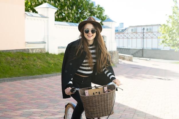 도시 주변에 자전거를 타고 모자와 안경에 젊은 여자