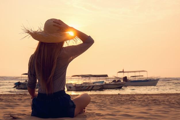 바다에서 석양을보고 모자에 젊은 여자