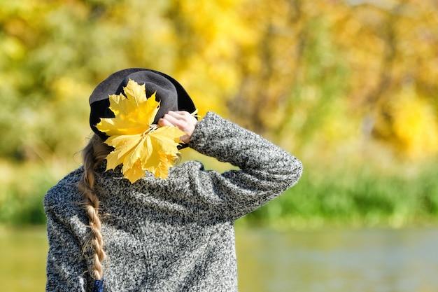 Молодая женщина в шляпе с кучей листьев стоит на берегу реки