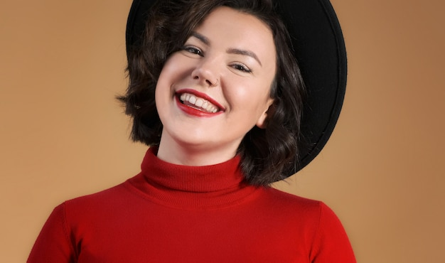Молодая женщина в шляпе с красными губами улыбается. портрет счастливой женщины. модель способа близкая вверх