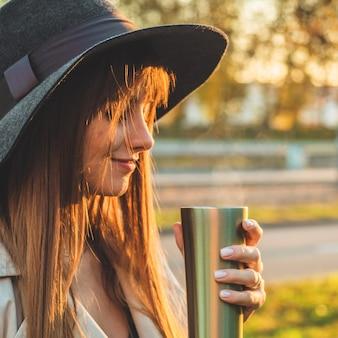 柔らかな日当たりの良い日光の下で魔法瓶サーモカップ屋外ポートレートと帽子の若い女性。秋。日没。居心地がいい。