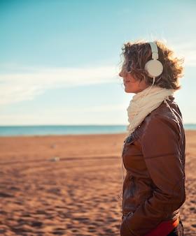 해변에서 헤드폰에서 젊은 여자
