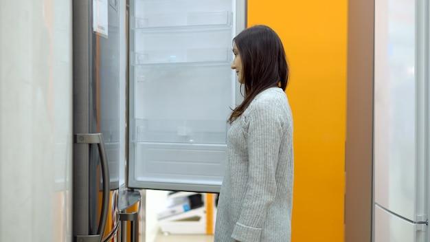 Молодая женщина в магазине бытовой техники выбирает холодильник.