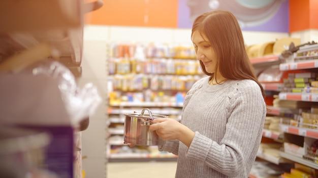 Молодая женщина в магазине товаров для дома выбирает кастрюлю.