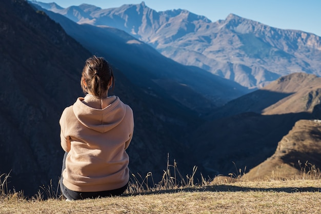 パーカーを着た若い女性が山を背景に地面に座って、背面図。