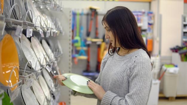 Молодая женщина в магазине товаров для дома выбирает тарелки.