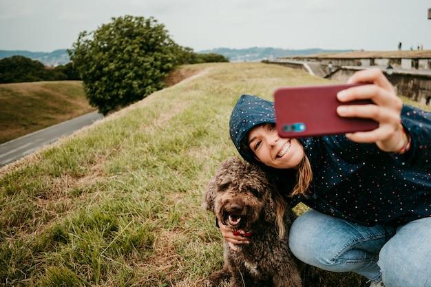 Молодая женщина в куртке с собакой