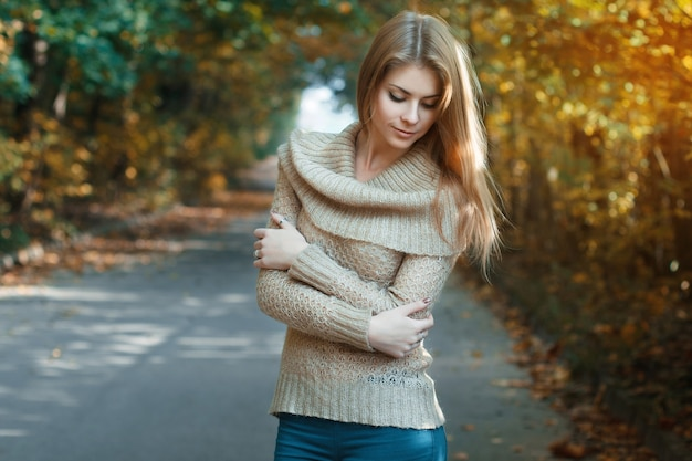 秋の公園に立っているジャージの若い女性