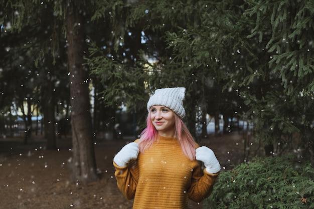モミの木と雪が降るに対してポーズをとるニット帽と白い手袋の若い女性。冬のファッション