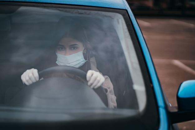 Молодая женщина в маске и перчатки за рулем автомобиля.