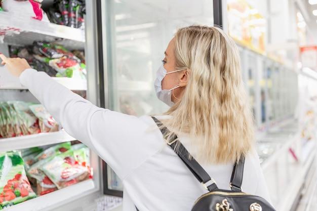 Молодая женщина в маске в продуктовом магазине в отделе замороженных продуктов