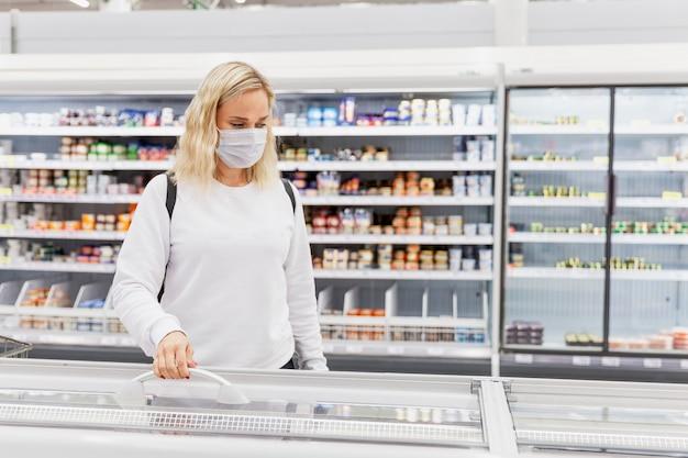 スーパーマーケットのマスクの若い女性が冷凍食品を選択します