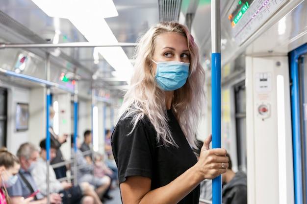 Молодая женщина в медицинской маске в вагоне метро.