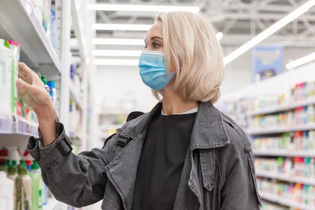 Молодая женщина в медицинской маске в супермаркете выбирает чистящие средства.