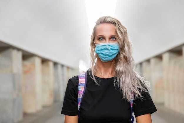 Молодая женщина в медицинской маске в вестибюле метро. красивая блондинка с длинными волосами в черной футболке.