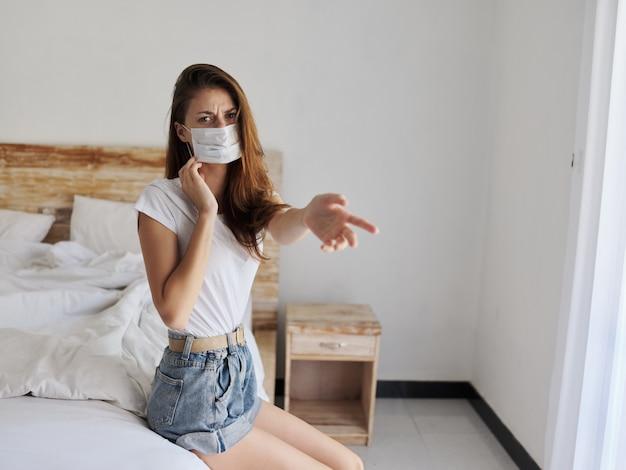 医療用マスクの若い女性がベッドに座って、横の隔離に彼女の指を示しています