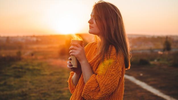 柔らかな日当たりの良い日光の下で魔法瓶サーモカップ屋外ポートレートとオレンジ色のセーターの若い女性。秋。日没。居心地の良い