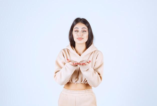 Молодая женщина в розовом балахоне дует любовь