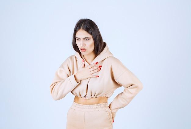 Молодая женщина в розовой толстовке с капюшоном качается и болит горло
