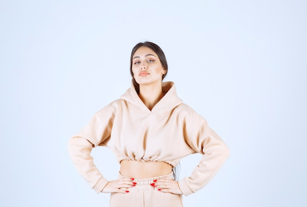 Молодая женщина в розовой толстовке с капюшоном принимает нейтральные позы