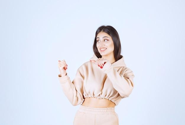 Молодая женщина в розовой толстовке с капюшоном, указывая назад