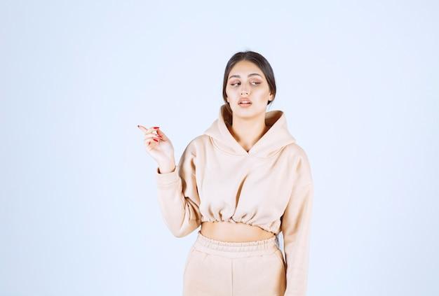 Молодая женщина в розовой толстовке с капюшоном, указывая за