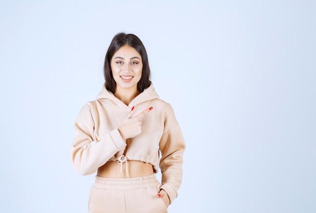 Молодая женщина в розовой толстовке с капюшоном, указывая куда-то вправо