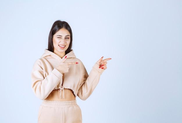 Молодая женщина в розовой толстовке с капюшоном, указывая вправо