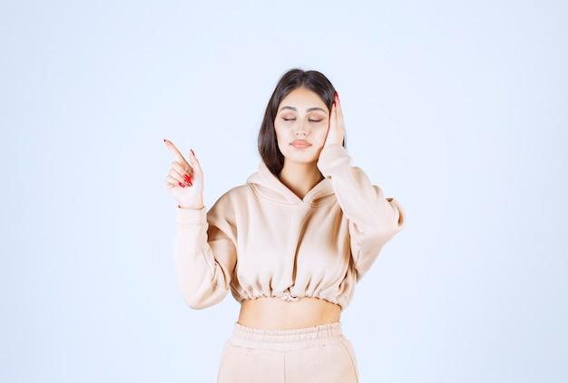 거꾸로 가리키는 분홍색 까마귀에 젊은 여자 무료 사진