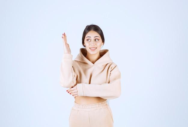 彼女の手を上げるピンクのパーカーの若い女性