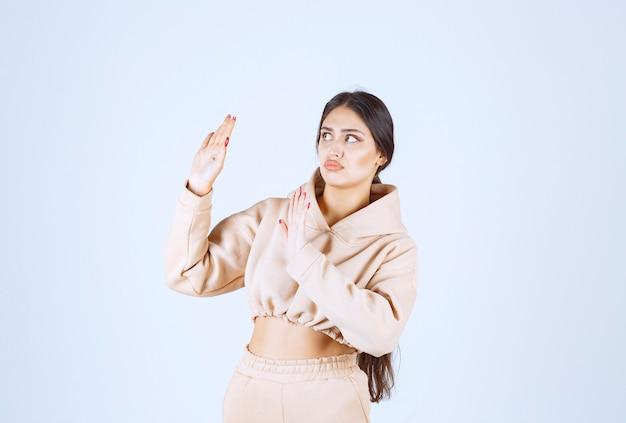 Молодая женщина в розовой толстовке с капюшоном останавливает нежелательную вещь
