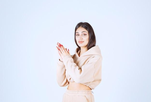 손을 결합하고기도하는 분홍색 까마귀에 젊은 여자