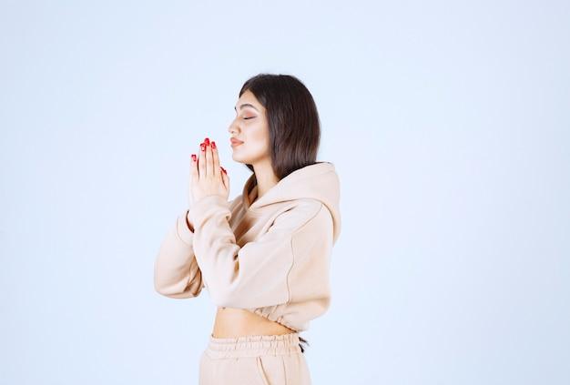 手を合わせて祈るピンクのパーカーの若い女性