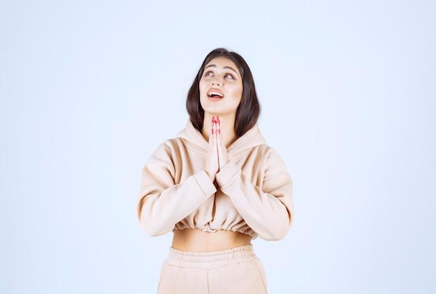 手を合わせて祈るピンクのパーカーの若い女性 無料写真