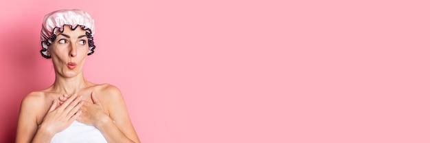 Молодая женщина в розовой шапочке для душа удивленно смотрит в сторону на розовом фоне.