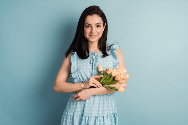 폴카 도트 드레스에 젊은 여자와 파란색 벽에 포즈 그녀의 손에 꽃