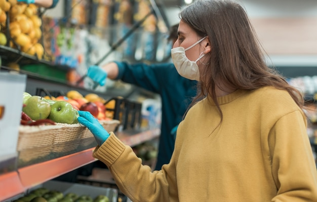 보호 마스크에 젊은 여자는 사과 구입