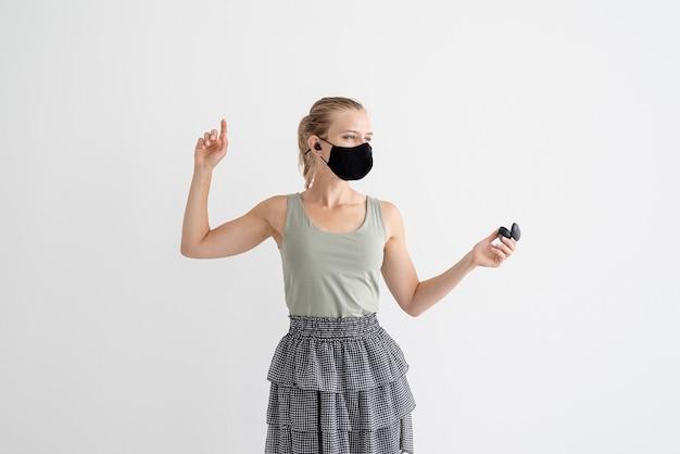 ワイヤレスイヤフォンを保持し、踊る保護マスクの若い女性