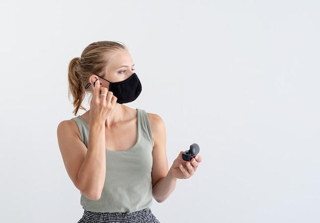 ワイヤレスイヤフォンを保持している保護マスクの若い女性