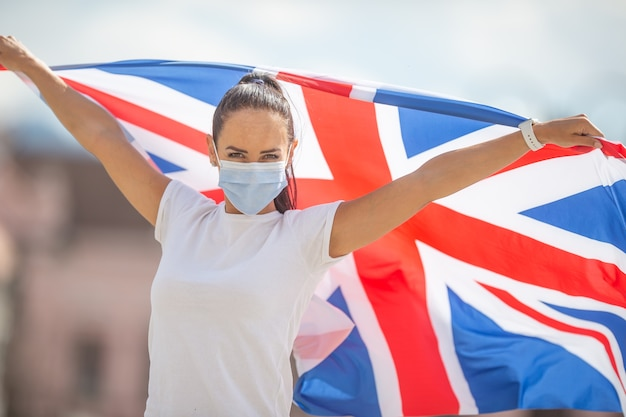보호 마스크를 쓴 젊은 여성은 전염병 동안 영국 국기를 들고 있습니다.