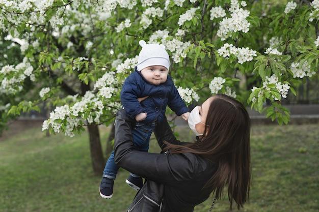 Молодая женщина в защитной маске играет со своим маленьким сыном на улице. covid-19