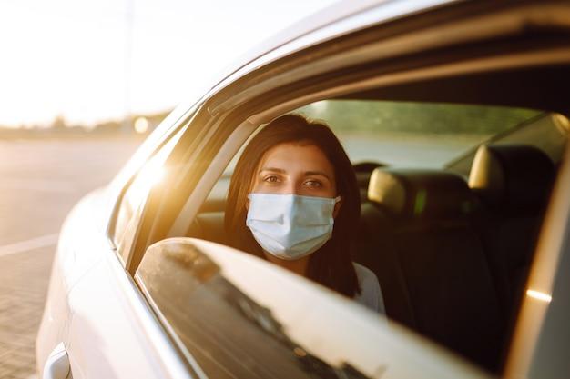 Молодая женщина в защитной маске сидит в машине